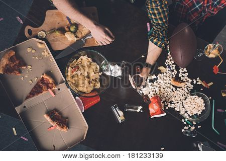 Partial Top View Of Man Holding Whiskey Bottle At Messy Table After Party