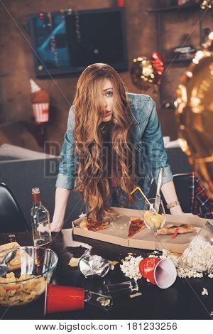 Depressed Young Woman With Hangover Leaning At Messy Table After Party