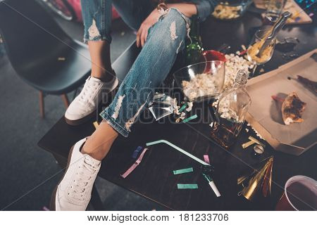 Woman Sitting On Table In Messy Room After Party