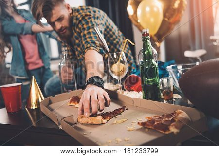 Man Eating Stale Pizza In Messy Room After Party