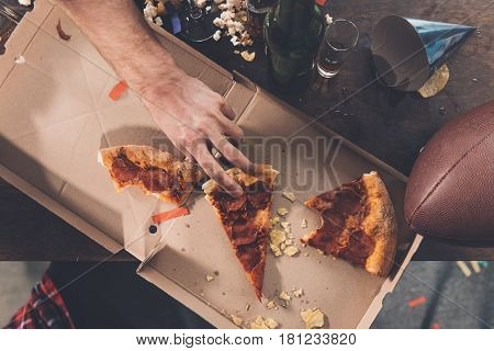 Top View Of Man Eating Stale Pizza In Messy Room After Party