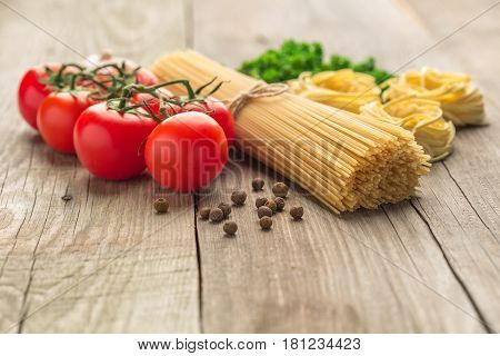 spaghetti and tagliatelle with ingredients for cooking pasta. Curly parsley garlic tomatoes on a blue background