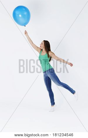 Young woman holding floating balloon studio shot