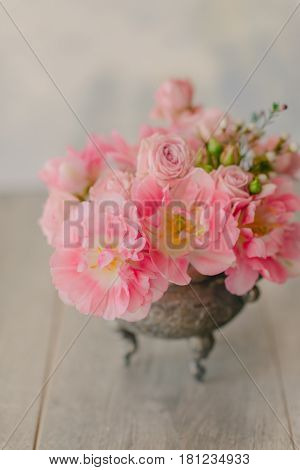 A bouquet of pink decorative tulips in an antique silver vase