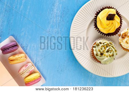 Cupcakes with buttercream. Macaroons in box. Sweet cake with pistachio nuts cream and small chocolate bar. Dessert with topping. Wooden background.