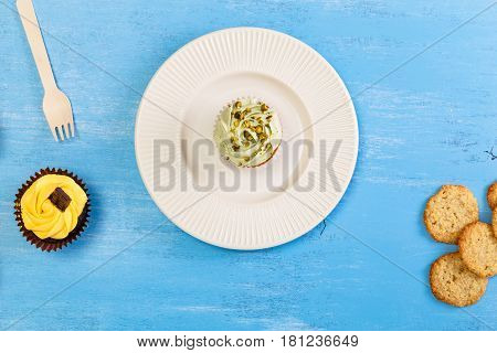 Cupcakes with buttercream. Sweet cake with pistachio cream and small chocolate bar. Dessert with topping. On blue wooden rustic background.