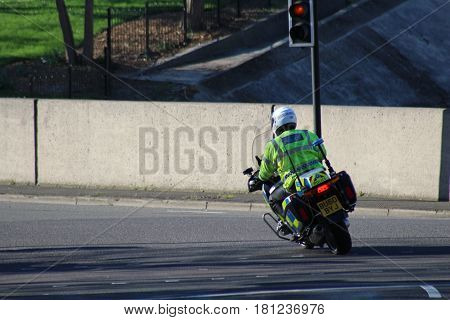 London, March 2017 - A London Metropolitan Police motorcycle speeds around a corner in South West London