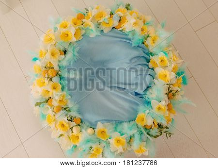On the floor lies a large floral wreath of daffodils with blue feathers
