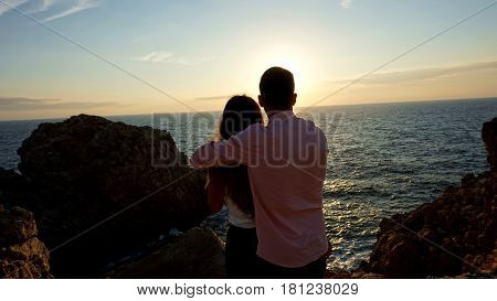 Couple in front of areddish sunset on a beach of the balearic islands