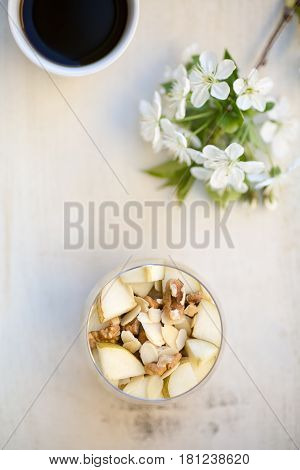 Oatmeal breakfast flavoured with mashed banana topped with sliced pear walnuts sliced almonds and honey view from above served in a clear round glass placed on a wooden light colored background together with cup of black coffee and cherry twig in bloom