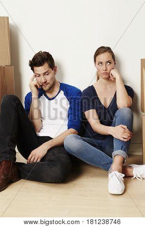 Bored couple amongst boxes looking away studio shot