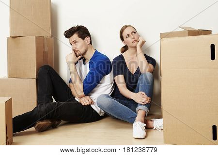 Annoyed couple sitting among boxes for moving home