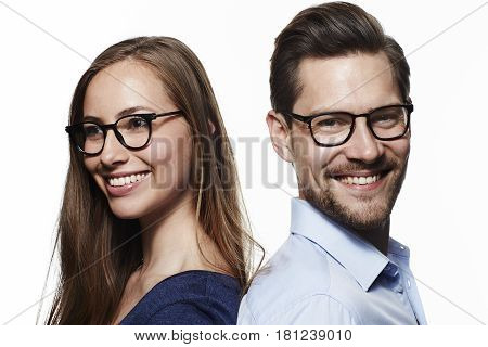 Happy couple wearing glasses smiling studio shot