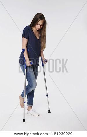 Injured woman on crutches in white studio