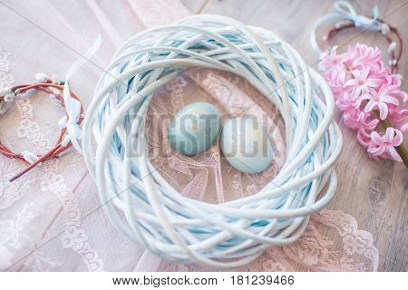 On a wooden blue background Easter eggs in a wicker nest and hyacinth