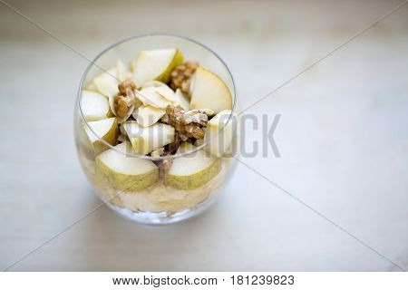 Oatmeal porridge flavored with mashed banana topped with sliced pear walnuts almonds and honey view from above served in a clear round glass placed on a wooden light colored background