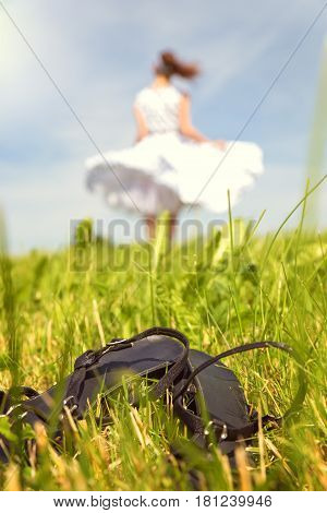Woman with a white petticoat dress is dancing on the meadow shoes in the front