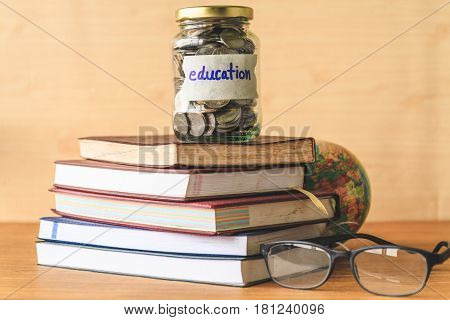 Coins in glass jar with education label book, glasses and globe on wooden table. Financial concept.
