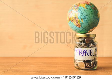 Coins in glass jar with travel label and globe on wooden table. Saving money for travel concept. Free space for text