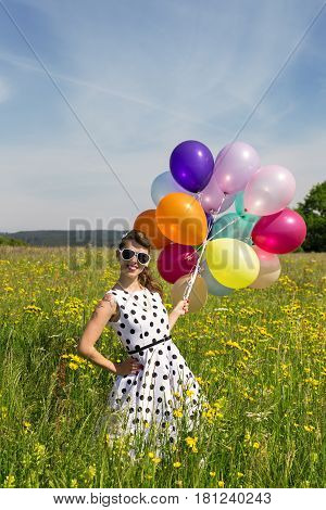 Smiling Rockabilly Girl with colorful balloons on a flowering meadow