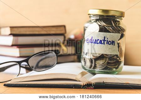 Coins in glass jar with education label, book, glasses and globe on wooden table. Financial concept.