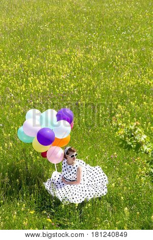 beautiful pinup girl with colorful balloons sitting on a flowery meadow topview