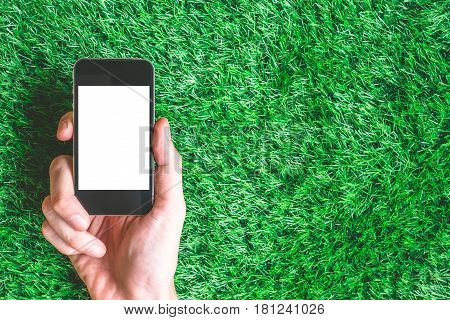 Male hand holding smart phone on green grass background. Free space for text