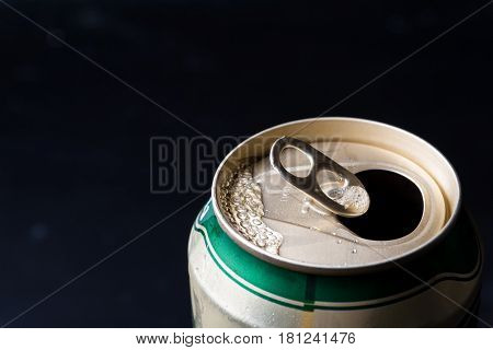 Close up of opened beer can on a black background.