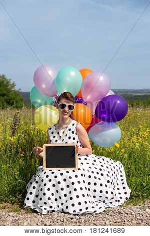 Rockabilly or pinup girl with colorful balloons on the road holding a board with copyspace
