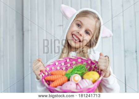 Blonde little girl is holding wicker pink basket which is full of Easter egg and toy carrots. She is wearing white kigurumi and resemble to a Easter bunny. The picture has a white background