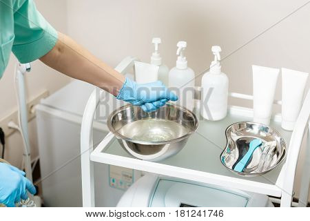 cosmetic Cabinet. beautician preparing for the procedure. the nurse wets the sponge in the water in bowl.  tools in medical basin on table.