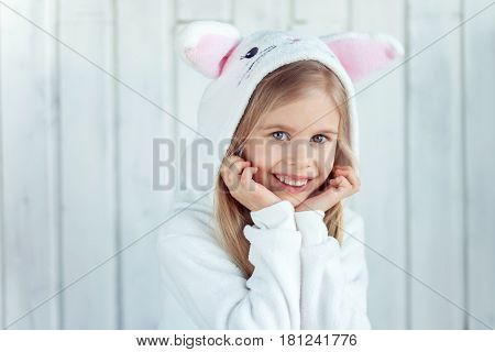 Little young girl is posing to camera. She is keeping her arms to her chin amd has a wide smile. Kid is wearing rabbit kigurumi. Easter bunny
