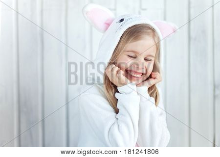 Blonde hair girl is giggling to camera. Kid is wearing white kigurumi reminds Easter bunny. The picture has white background