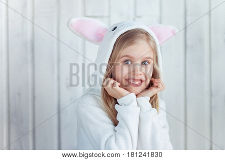 Little pretty girl wearing rabbit kigurumi is looking to a camera with surprise emotion on her face. Easter bunny.