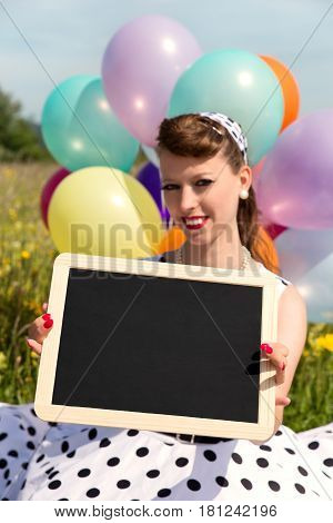 smiling woman with a vintage dress from the 60´s holding a board with copyspace concept Retro and vintage