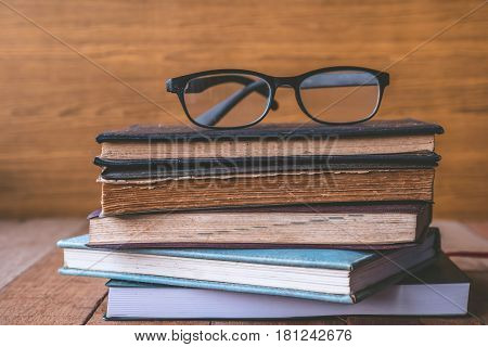 Old hardback book with glasses on wooden table.