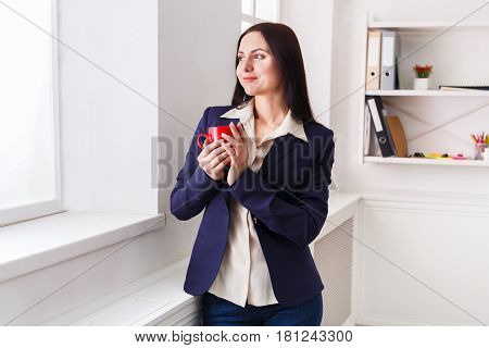 Coffee break. Ambitious elegant business woman in formal wear standing at workplace and looking through window