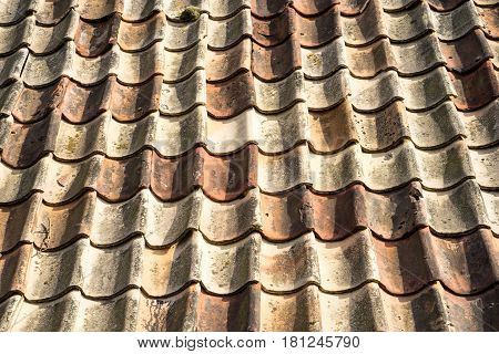 closeup of vintage tile roof with light and dark brick. The roof is old and many of the tiles are cracked