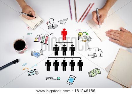 People pyramid with one leader at the top and silhouettes at all levels, business Concept. The meeting at the white office table.