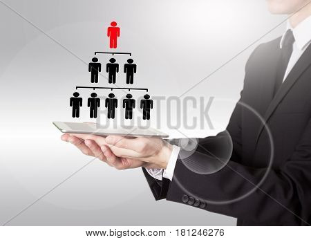 People pyramid with one leader at the top and silhouettes at all levels. Young man holding a tablet computer.