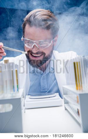 Bearded Chemist In Goggles With Reagents In Tubes And Tablet In Laboratory