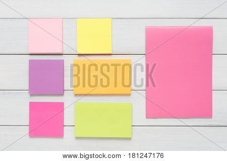 Memo sticky notes, bad memory concept. Flat lay of colorful paper stickers on white rustic wooden board background, top view with copy space, nobody, objects