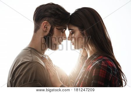 Head to head. Woman holding hands on man's chest. Man touching woman's head. Bright background.