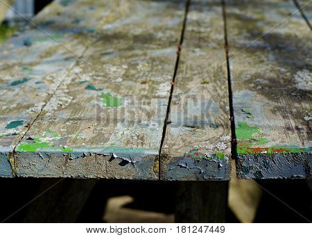 Old weathered picnic table with multi color flaking paint.  Horizontal, well used wood