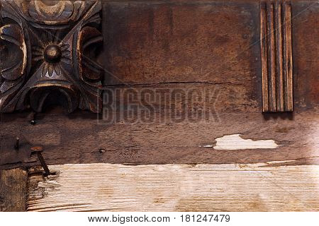 Background of wooden dark brown rosettes Hand-carving on wood Vintage close-up of a plaque with carved pattern with place for text rusty nail