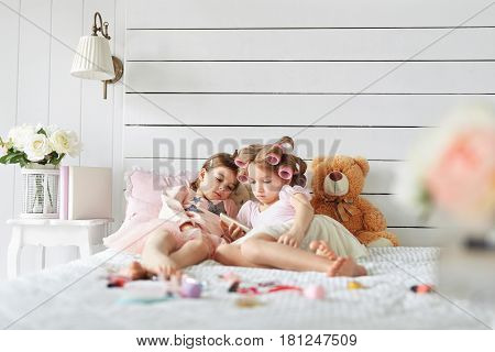 Two pretty girls are laying on the bed in a fancy bedroom full of different toys and flowers. One girl is holding mobile phone and showing it her friend.