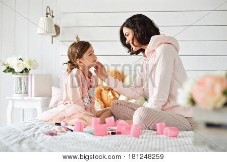 Beautiful young mother is doing make up to her daughter. She is looks like a princess with her fancy skirt and crown. They are sitting on a bed with a mess of toys and curlers