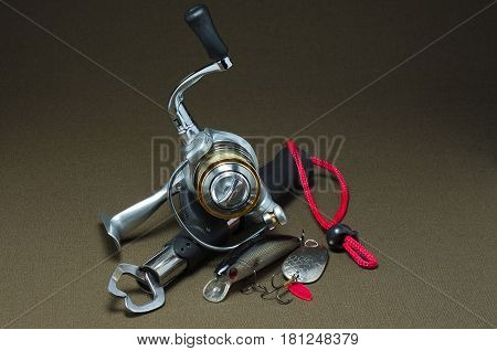 Fishing reel with lures and capture on a dark background