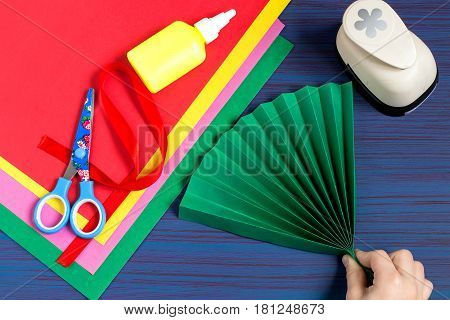 Making gift for Mother's Day by the child. Colorful bouquet of flowers out of paper. Children's art project. DIY concept. Step-by-step photo instruction. Step 2. Child folds a fan of green paper