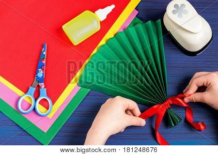Making gift for Mother's Day by the child. Colorful bouquet of flowers out of paper. Children's art project. DIY concept. Step-by-step photo instruction. Step 3. Child tying a bow on a paper fan